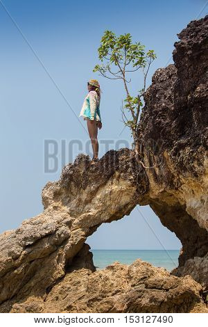 Girl standing on coastal sea rocks. Well being healthy lifestyle.
