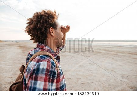 Happy african american young man with backpack standing on the beach and looking far away