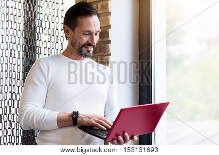 Better connection. Vivacious bearded man standing near window holding laptop and looking at it.