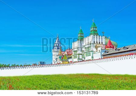 The white bridge and richly decorative central gates lead to Izmailovsky Kremlin the center of cultural development and family rest Moscow Russia.