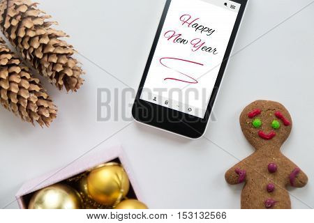 Flat view of a phone among cute Happy new year decoration, cones, box of glass balls, ginger man. New year concept, high angle, closeup