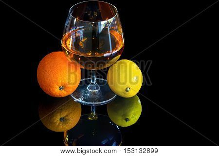 Snifter of brandy and lemon with orange on black background