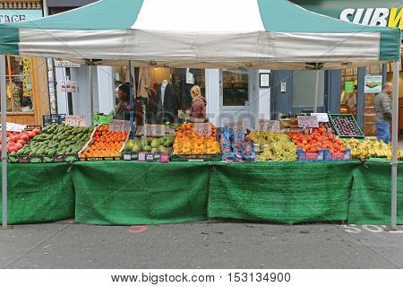 LONDON UNITED KINGDOM - NOVEMBER 24: Brick Lane Market in East London on NOVEMBER 24 2013. Temporary Street Market Stall With Fruits and Vegetables at Sunday in London United Kingdom.