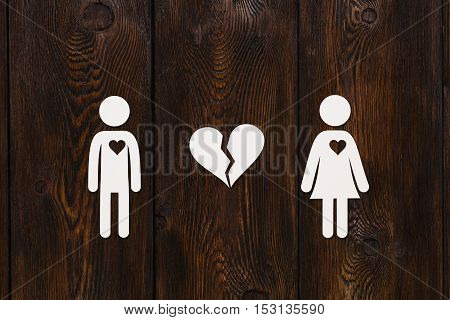 Paper man, woman and broken heart on dark wooden background. Love, relation concept. Abstract conceptual image
