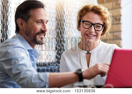 Successful results. Bearded man and pointing at laptop screen while discussing business deals with smiling red-haired woman.