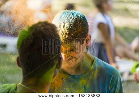 Lviv Ukraine - August 28 2016: Guys pummel each other colored powder during the festival of color in a city park in Lviv.