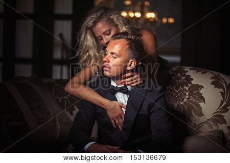 Woman warping her arms around man in suit