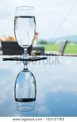 Glass of water with reflex on nature background.