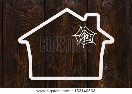 Paper house with web, copyspace on dark wooden background. Housing, helloween concept. Abstract conceptual