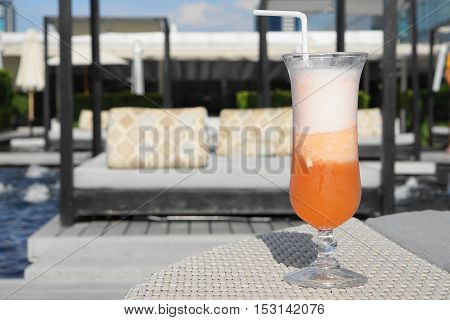 sour orange cocktail with sun bathing bed as background - evening sunlight