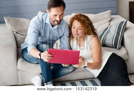 Testing new gadget. Handsome bearded man sitting on couch, holding new laptop near his wife sitting on floor