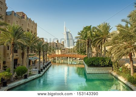 DUBAI, UAE - OCTOBER 06, 2016: The iconic Burj al Arab seven star hotel in Dubai taken set against the azure waters of the artificial lake in Madinat Jumeirah surrounded by palm trees