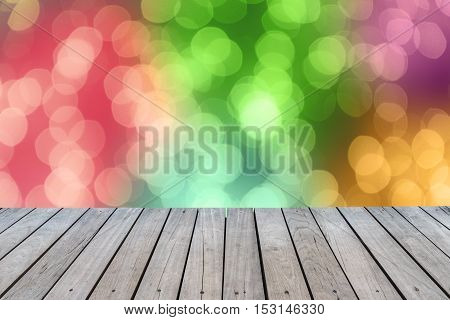 Blurred bokeh light background from christmas night with wooden floor