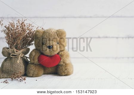 Teddy bear holding red heart shape with dried flower on white woden background