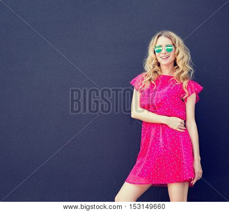 Fashion Woman in Pink Dress and Sunglasses at the Dark Textured Wall Background. Urban Fashion Girl in Summer Concept. Street Style Female. Toned Photo with Copyspace.