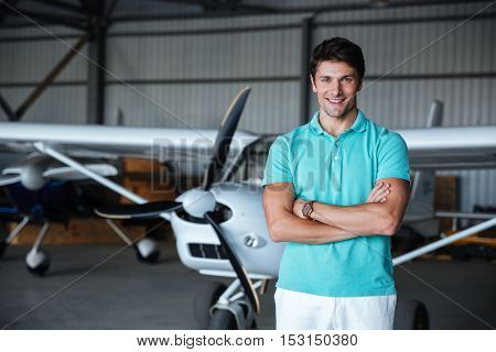 Cheerful young man standing with arms crossed near small plane