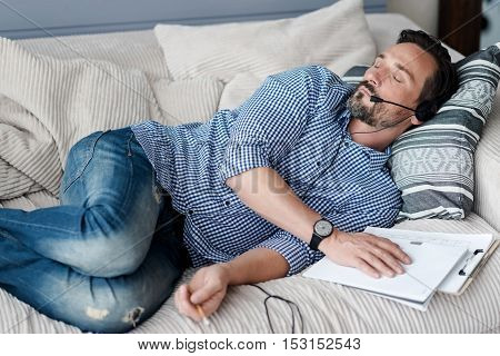 Taking nap. Top view of aged bearded man wearing headphones with microphone lying on coach and sleeping.