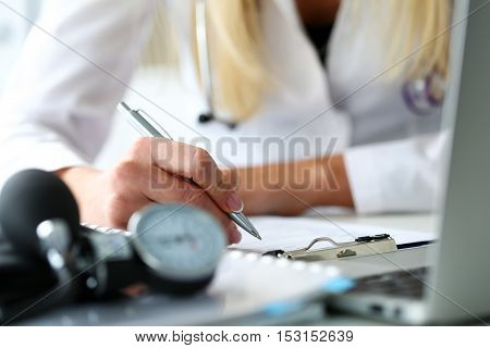 Female medicine doctor hand holding silver pen looking in clipboard pad closeup. Ward round patient visit check 911 medical calculation and statistics concept. Physician ready to examine patient