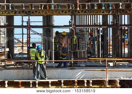 Workers Working Amongst Scaffolding And Concrete On Contruction Site