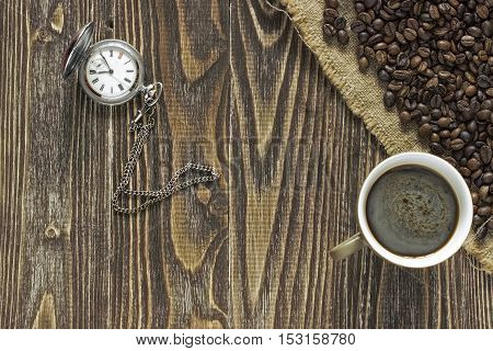 A pocket watch with a cup of coffee and crema is in the corner of a wooden table on a burlap canvas close to crumble coffee beans. Close up. Top view