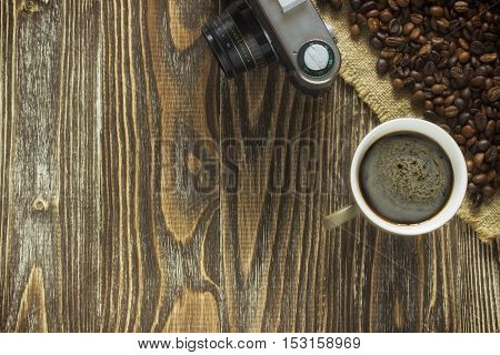 Obsolete vintage camera and a mug of coffee with crema and the coffee beans standing on a burlap canvas on a wooden background. Colose up. Top view