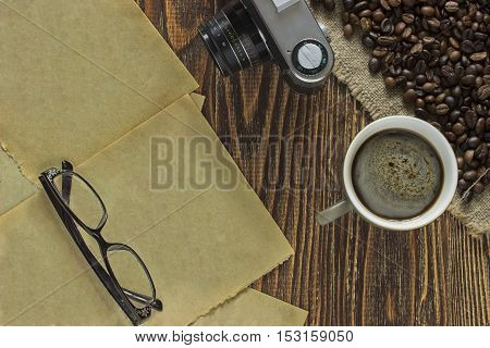 Old torn pages of the textbook with glasses lying near the outdated camera and a cup of coffee with crema and coffee beans on burlap canvas on a wooden table. Close up. Top view
