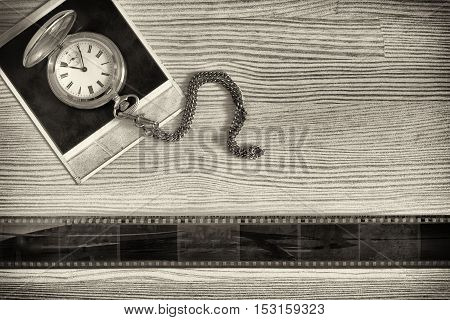 Photo old pocket watch lying on outdated vintage photograph next to a tape of film collage of nostalgic photos. Black and white photo. Top view. The frames on the film are abstraction
