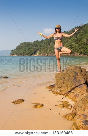 Girl standing on in yoga pose coastal sea rocks. Well being healthy lifestyle.