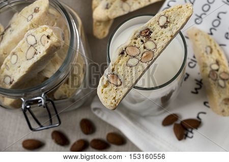 close up of tub of biscotties and glass of milk standing on cloth with almonds