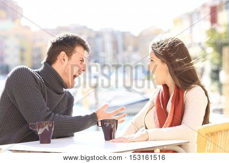 Angry casual couple arguing and shouting each other in a bar terrace outdoors with a vacational port background. Disagreement concept