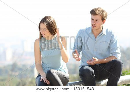 Angry couple arguing outdoors in a park with city in the background
