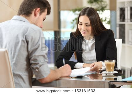 Client signing a document in an office with a businesswoman looking the contract