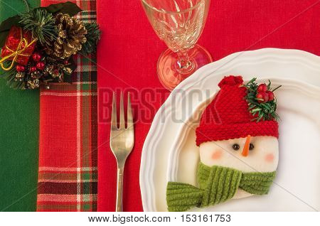 Holiday table setting with two white plates fork wineglass and Christmas decorations over colorful napkins. Top view. Horizontal.