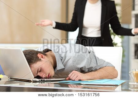 Employee sleeping with the face over the laptop with his angry boss watching back at office