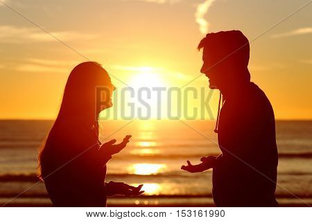Side view of two friends or couple silhouette of teens talking happy on the beach at sunset with the sun in the middle and a warmth light