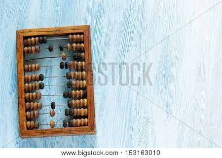 Old wooden scratched vintage decimal abacus on a blue wooden board for the background. Top view. Flat lay.