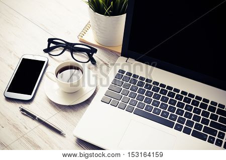 Still life photo of laptop notepad coffee glasses and other stuff on wooden table