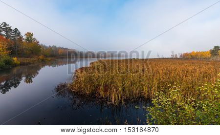 Morning mist and fog rises from warm water into autumn October air on Corry lake, Ontario, Canada.