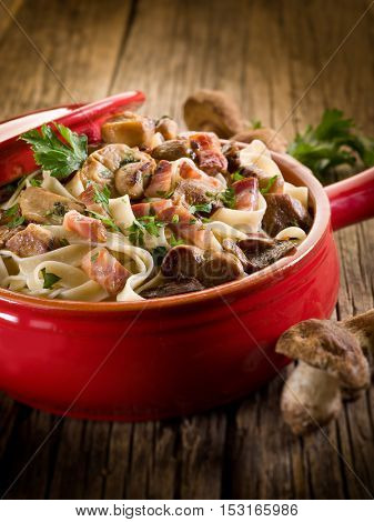 tagliatelle with cep edible mushroom and bacon, selective focus