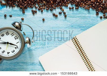 Single simple empty white notebook with a blank for drawing or writing scattered roasted coffee beans and alarm clock with silver metal bells are on a Desktop from blue wooden plank. Top view. Mock up. Flat lay
