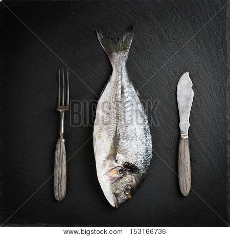 Top view of fresh dorado fishes or giltheadvintage fork and knife on a black slate board.