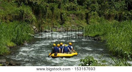 A GROUP OF MEN AND WOMEN, WITH A GUIDE, WHITEWATER RAFTING