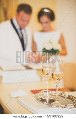 Wedding glasses are in the foreground. Blurred outlines newlyweds seen in the background.