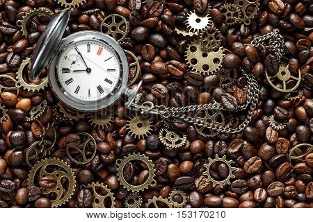 mock up for background in steampunk style. Roasted coffee beans mixed with brass gears and old pocket watch. Grunge style toned. Top view.