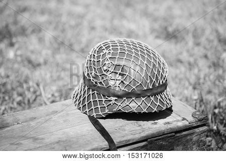 Close Metal Helmet Of Infantry Soldier Of Wehrmacht, Nazi Germany Of World War II On Old Wooden Box
