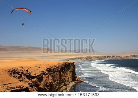 Paraglider soaring over the cliffs at oceanfront of Paracas Peru
