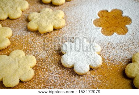 Homemade shortbread flower shape cookies with sugar powder on wooden table, top view