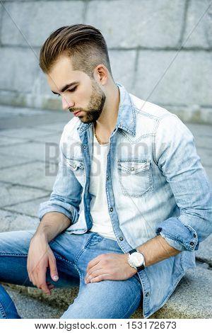 Handsome bearded man wearing jeans shirt, portrait shot in urban area