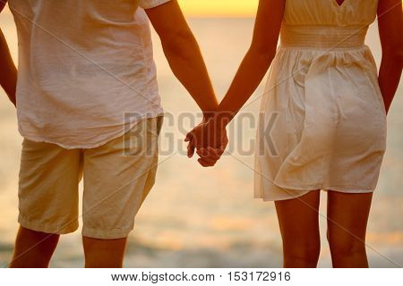 Romantic couple holding hands on beach sunset during travel. Closeup of happy woman and man together in romance on romantic honeymoon getaway in beautiful light. Casual beachwear white linen clothing.