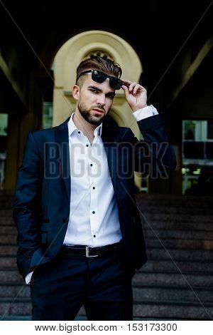 Handsome bearded man wearing suit, portrait shot in urban area